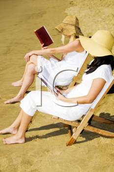 Royalty Free Photo of Two Women Reading on the Beach