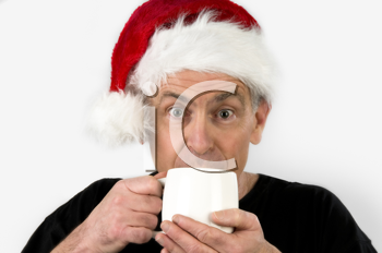 Royalty Free Photo of a Man in a Santa Hat Drinking Coffee