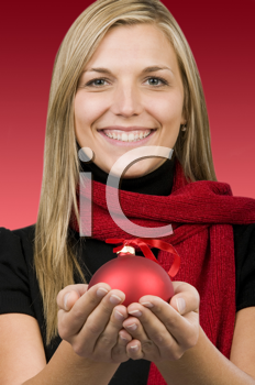 Royalty Free Photo of a Woman Holding a Red Ornament in the Palms of Her Hands