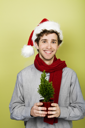 Royalty Free Photo of a Man in a Santa Hat Holding a Tree