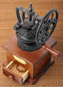 Antique hand-mill for coffee on a wicker mat.