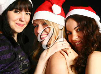 three 20-25 years women  friends having fun on a christmas party