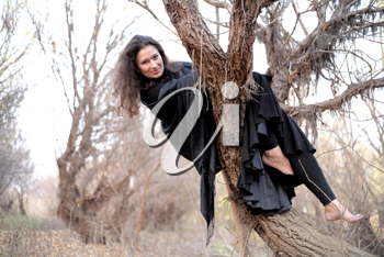 Shot of a gothic woman in a autumn park. Halloween.