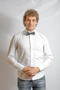 Fashionable boy blank expression. Curly hair, white shirt. Bow tie for something funny
