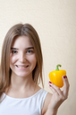 beautiful girl with yellow sweet pepper - organic food and health concept.