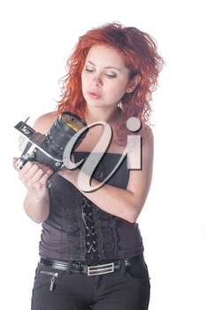 Photo of a beautiful female with red hair holding an old film camera.
