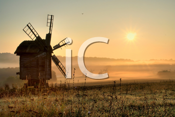 Royalty Free Photo of a Windmill in a Field at Sunrise