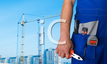 Royalty Free Photo of a Worker Holding a Tool With a Building in the Background