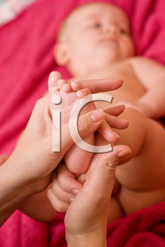 Royalty Free Photo of a Mother Massaging Her Baby's Feet