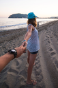 Girl holding a hand man on the beach in Alanya, Turkey