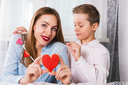 Happy Valentines Day or Mother day. Young boy and mum celebrate with gingerbread heart cookies on a stick.