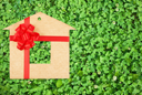 Royalty Free Photo of a Background of a Bed of Green Clovers With a Symbol of a Home Made Out of Cardboard With a Red Bow and Ribbon