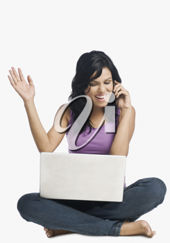 Woman with a laptop and talking on a mobile phone