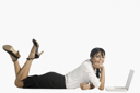 Woman lying in front of a laptop and smiling
