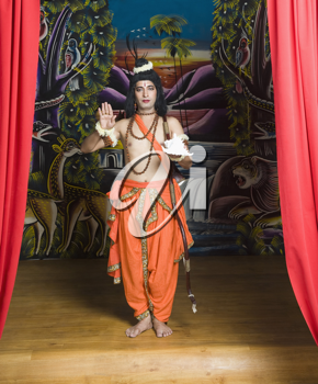 Stage artist dressed-up as Rama blessing and holding a conch shell