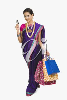 Portrait of a woman carrying shopping bags and a credit card
