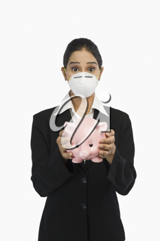 Businesswoman wearing an H1N1 mask and holding a piggy bank