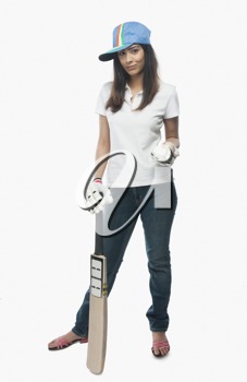 Portrait of a female cricket fan holding a bat and a ball