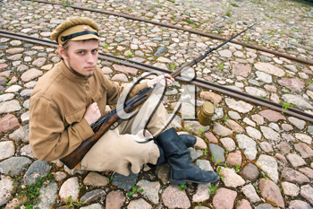 Royalty Free Photo of a Soldier Sitting on the Ground