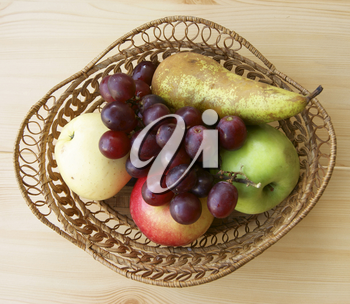 Ripe fruits in braided basket on table