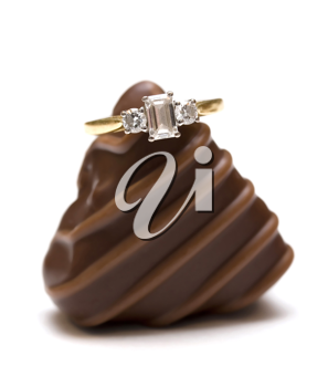 Diamond engagement ring resting on a chocolate, isolated over white