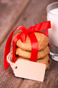 Glass of milk and a stack of homemade cookies, tied with a red ribbon and a gift tag, with space for your text, over old wooden background.