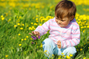 Royalty Free Photo of a Child Playing With Flowers