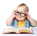 Royalty Free Photo of a Little Boy With Glasses and a Book