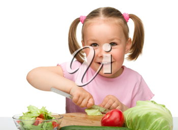 Royalty Free Photo of a Little Girl Cutting Vegetables