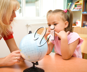Royalty Free Photo of a Little Girl With a Teacher Looking at a Globe