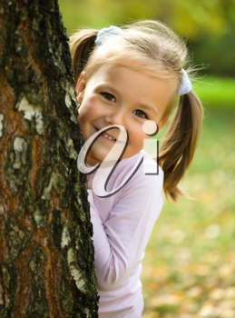Royalty Free Photo of a Girl Looking Out From Around a Tree
