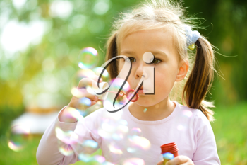 Royalty Free Photo of a Little Girl Blowing Bubbles