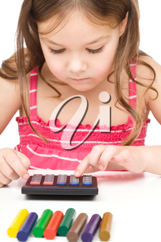 Little girl is playing with calculator, isolated over white