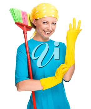 Young woman - cleaning maid holding broom and putting on yellow gloves, isolated over white