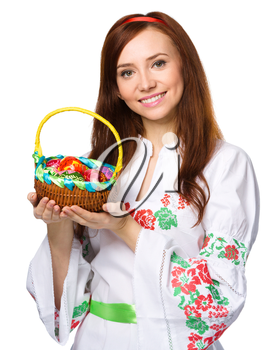 Young woman in ukrainian national cloth is holding a basket full of easter eggs, isolated over white