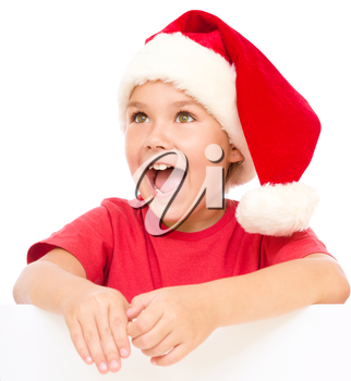 Little girl in santa hat is holding blank board and screaming, isolated over white