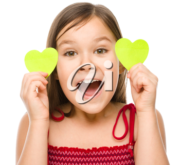 Little girl is holding hearts near her eyes, valentine concept, isolated on white