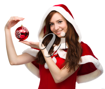 Young happy woman in santa cloth is holding a christmas decoration, isolated over white