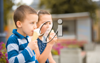 Two children are eating ice-cream outdoors