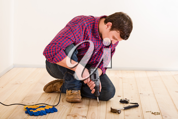 Young worker with screwdriver installing wooden flooring in the room