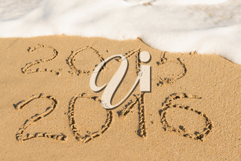 digits  2015 and 2016 on the sand seashore - concept of new year and passing time