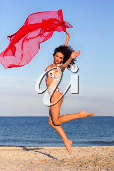 Cute young woman jumping on the beach
