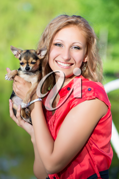 Cheerful blond woman posing with a small dog