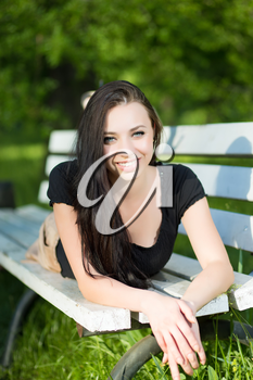 Young smiling brunette lying on the bench