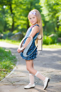 Adorable blond girl posing in jeans dress outdoors