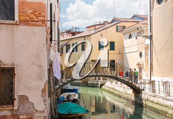 VENICE, ITALY - MAY 06, 2014: Picturesque bridge over a narrow canal in Venice, Italy