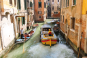 VENICE, ITALY - MAY 06, 2014: People in boats  move along a canal in Venice, Italy