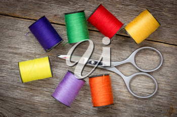 Scissors and spools of colored thread on the wood background
