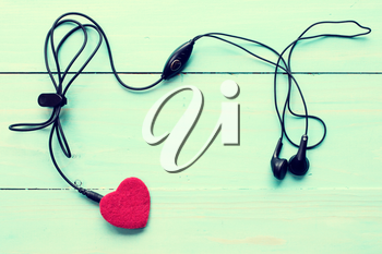 Concept for love music. Earphones connected to the heart. Image toned with retro filter.