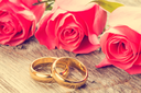 Wedding rings with pink roses on wooden background